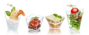 Variety of appetizers in transparent glasses. Snacks. Finger food.